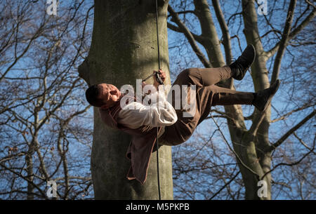 Male acrobat in woodland as part of outdoor theatre performance by Whispering Woods Folk, at Hodscock Priory, Nottinghamshire, - Stock Image