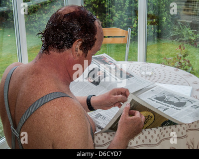 Middle-aged man reading newspaper while hair-dye is colouring his hair.Wearing braces, sitting in conservatory. - Stock Image