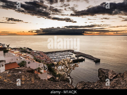 View westwards at sunset over the harbour of Los Gigantes, Tenerife, Canary Islands towards the island of La Gomera - Stock Image