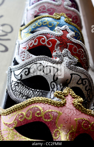 Masquerade masks for the ball, hanging in a row on a wall - Stock Image
