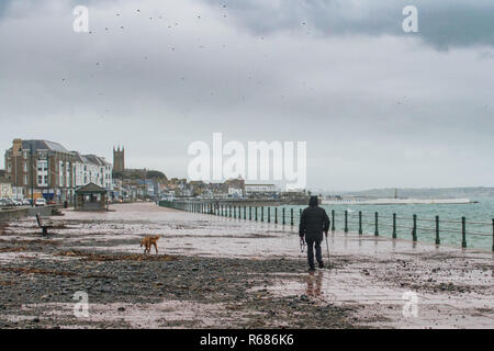 Penzance, Cornwall, UK. 4th December 2018. UK Weather. As Storm Etienne starts to approach Cornwall and the South West of england winds are increasing in speed and waves are once more crashing onto the seafront at penzance, and depositing large amounts of seaweed and rocks on the pavement and road. Credit: Simon Maycock/Alamy Live News - Stock Image