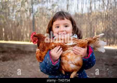 Portrait of happy toddler girl holding chicken - Stock Image