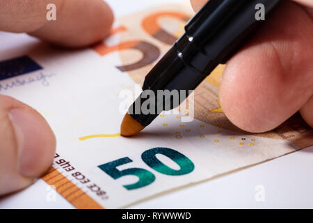 Close-up Of Hand Writing On Banknote With Yellow Marker - Stock Image