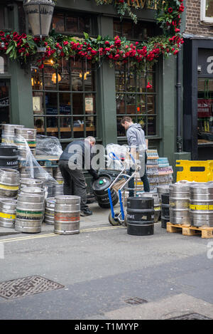 Two men at work moving a delivery of beer kegs into the cellar of Mr Fogg's Tavern, a London public house. - Stock Image