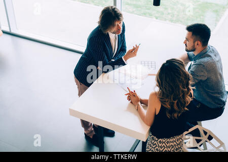 Businessman discussing with colleagues at desk in office - Stock Image