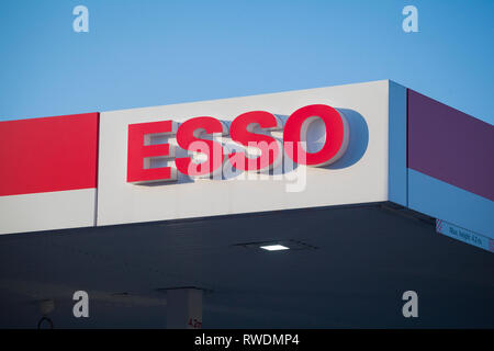 The Esso sign on the side of a garage against clear blue sky. - Stock Image