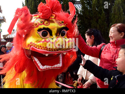 Kaifeng, China's Henan Province. 16th Feb, 2019. Visitors watch a lion dance performance on a temple fair to celebrate the upcoming Lantern Festival, which falls on Feb. 19 this year, in Kaifeng City, central China's Henan Province, Feb. 16, 2019. Credit: Zhu Xiang/Xinhua/Alamy Live News - Stock Image