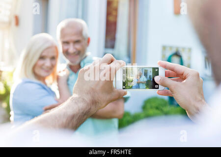 Man photographing senior couple with camera phone - Stock Image