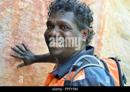 Aboriginal guide pointing out artwork in a rock art gallery on Injalak Hill, Arnhem Land, Northern Territory, Australia - Stock Image