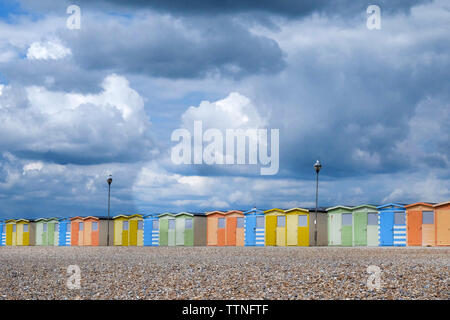 A line of 22 colorful Beach huts running through the centre of the image, below is a yellow pebble beach and above is a dramatic blue and white cloudy - Stock Image
