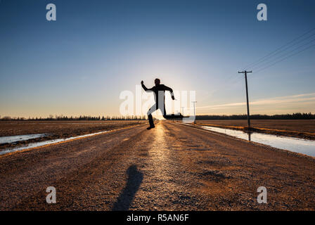 Sillhouette of the man skipping over the road - Stock Image
