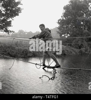 1960s, historical, a young adventure scout and team crossing a river on a rope bridge the scouts have  tied to a tree on the riverbank, England, UK. - Stock Image