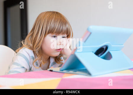 funny face expression of three years old blonde child sitting indoor, with head over hand watching digital tablet on table - Stock Image