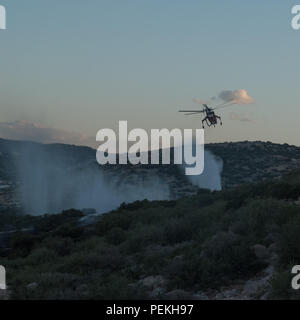 Emergency fire services spraying water preventing the fire from spreading further on the mountains. Saronida, East Attica, Greece, Europe. - Stock Image