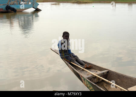 A young local boy sitting at the stern of a pirogue (traditional boat) on the River Bani. Mopti Region, Mali, West - Stock Image