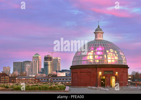 LONDON, UK - DECEMBER 13: Greenwich underpass entrance in early morning, with Canary Wharf skyscrapers in the background and pink tinted clouds in the - Stock Image