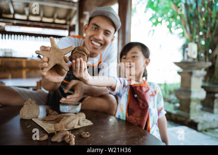 asian father and daughter making pottery together with clay - Stock Image