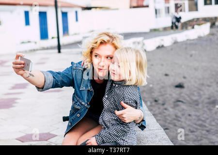 Young beautiful blonde caucasian mother and nice son children hugging and taking a selfie together in outdoor leisure activity - family love concept f - Stock Image