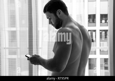 Good looking, muscular shirtless man using mobile phone next to balcony with city view - Stock Image