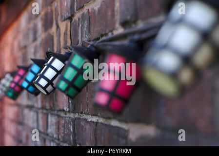 String of coloured lights against a brick wall - Stock Image