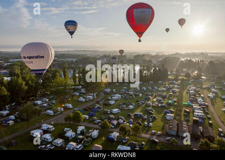 Balloons floating above spectators at the Northampton Balloon Festival at sunrise. - Stock Image