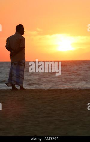 Man silhouetted at sunset Negombo beach Sri Lanka - Stock Image