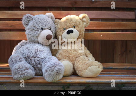 Two teddy bears sitting on a bench in a garden. - Stock Image