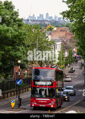 London, England, UK - June 1, 2019: A London double-decker bus climbs Old Church Road in Chingford, with the skyline of London's Docklands business di - Stock Image
