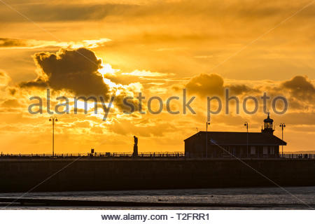 Morecambe, Lancashire, UK, 2 April 2019. UK Weather: A beautiful sunset over the Stone Jetty and Morecambe Bay. The spectacular sunsets at Morecambe have been an enduring attraction for visitors over many decades. Credit: Keith Douglas News/Alamy Live News - Stock Image