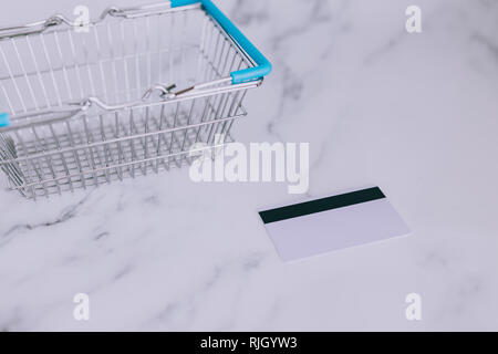 payment card on marble desk next to empty shopping basket, concept of budgeting for your expenses - Stock Image