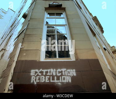 Glasgow, Scotland, UK. 14th July, 2019. Extinction Rebellion Summer Uprising #PaintTheStreets started with a warning of Mondays planned stint as they took to the streets to paint logos all over the city to advertise their power in an ominous way, maintaining secrecy with the willingness to graffito. Credit: Gerard Ferry/Alamy Live News - Stock Image