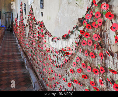 Fishing nets adorned with poppies on the north wall of the parish Church of the Holy trinity and All Saints at Winterton-on-Sea, Norfolk, UK, Europe. - Stock Image