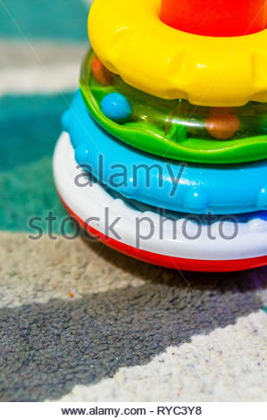 Detail of colorful rings of a stacking toy on a carpet in soft focus. - Stock Image