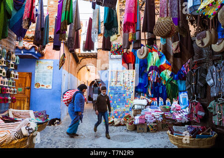 Chefchaouen, Morocco : A woman and a child walk past handicraft stalls in the blue-washed alleyways of the medina old town. - Stock Image