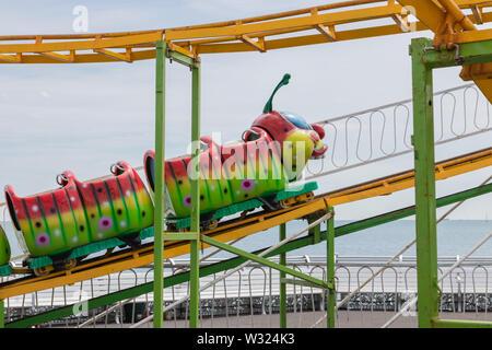 A child's caterpillar roller coaster at a funfair - Stock Image