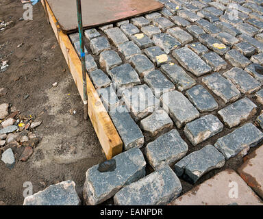 Traditional cobblestone drive being laid by hand by a skilled craftsmen in the construction industry. - Stock Image