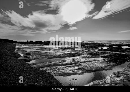 A black and white photograph of rock pools next to a pebble beach behind is the sea and a clear sky with white clouds, the sun is low in the sky back  - Stock Image
