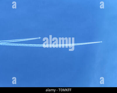 Crossing of airline lines on the blue sky above planet Earth - Stock Image