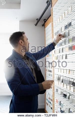 Male interior designer looking at swatches in design studio - Stock Image
