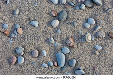 Water smoothed stones and sand on Lake Ontario beach at Lynde Shores Conservation Area in Whitby Ontario Canada - Stock Image