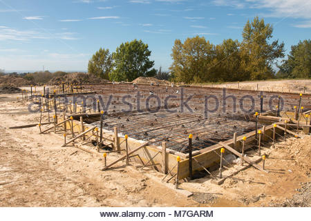 Reinforcing metal bars on foundation and floor ready for pooring concrete - Stock Image