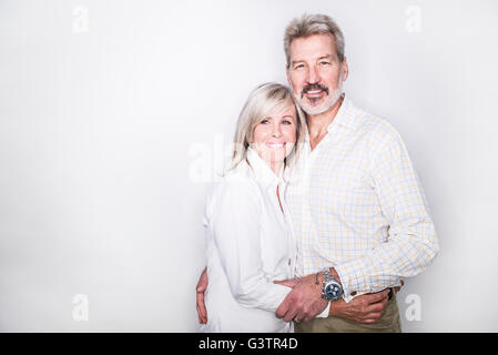 A mature couple posing in a studio looking happy. - Stock Image