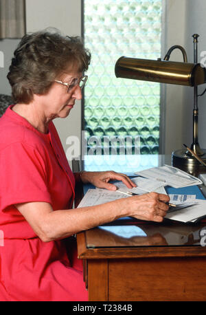 Senior Woman Paying Bills at her - Stock Image