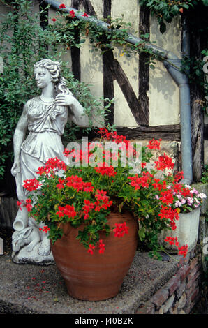 Courtyard of a house with Geranium planted  container and classical statue - Stock Image