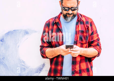 Coloured hipster people adult man with beard usgin modern cellular smart phone - standing on a white wall background - alternative job and work office - Stock Image