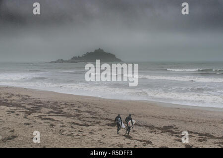 Marazion, Cornwall, UK. 1st December 2018. UK Weather. It was a dark, damp and misty afteroon on the beach at Marazion this afternoon. A handful of people were walking on the beach, and surfers were making the most of the waves. Credit: Simon Maycock/Alamy Live News - Stock Image