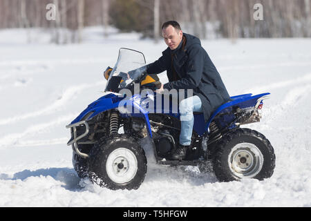 A winter forest in daylight. A man riding a big blue snowmobile. Side view - Stock Image