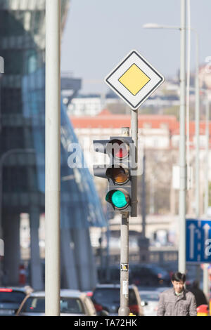 Traficlight green on the background of blurred city, cars and people - Stock Image