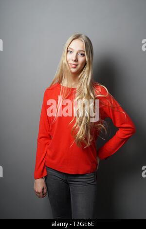 young teenage woman with long blond hair standing in her room against gray wall - Stock Image