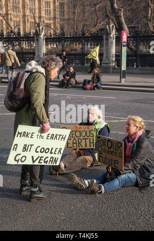 Three senior women of retirement age in the road by Parliament Square, Westminster for the Extinction Rebellion demonstration - Stock Image